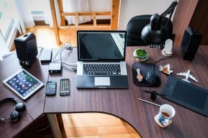 laptop, iphones, tablet, headphones, mouse, and other technology all sitting on a wooden table.